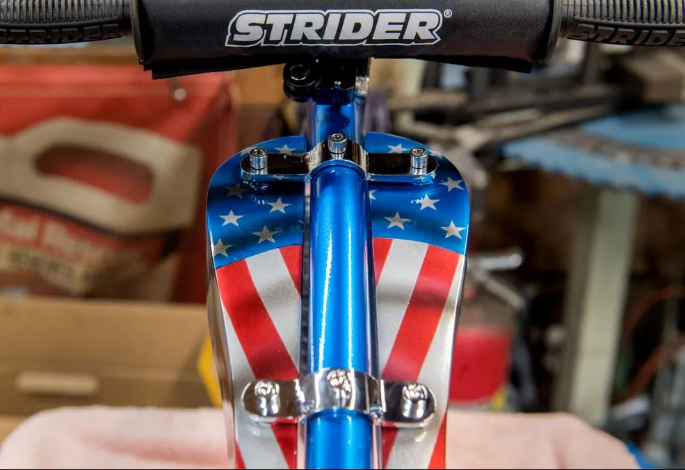 A dummy gas tank hangs from the frame of the customized Tiny Strider bicycle designed by famed motorcycle customizer Carl Pusser and granddaughter Jocelyn Dunn.